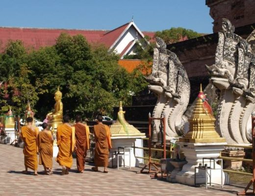 Monks walking by temple in Chiang Mai, Thailand