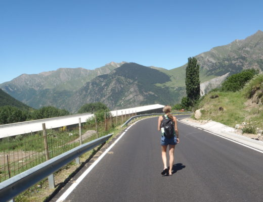 Girl walking solo on a backroad in Spain with mountains in the background