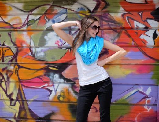 Lauren in sleeper scarf next to graffiti wall