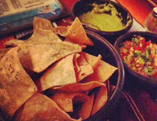Photo of nachos with guac and salsa on table
