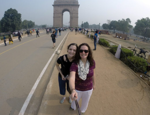 Two girls with selfie stick in front of India Gate in Delhi