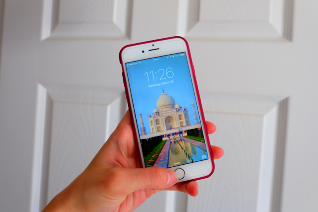Hand holding an iPhone with the Taj Mahal as the background.