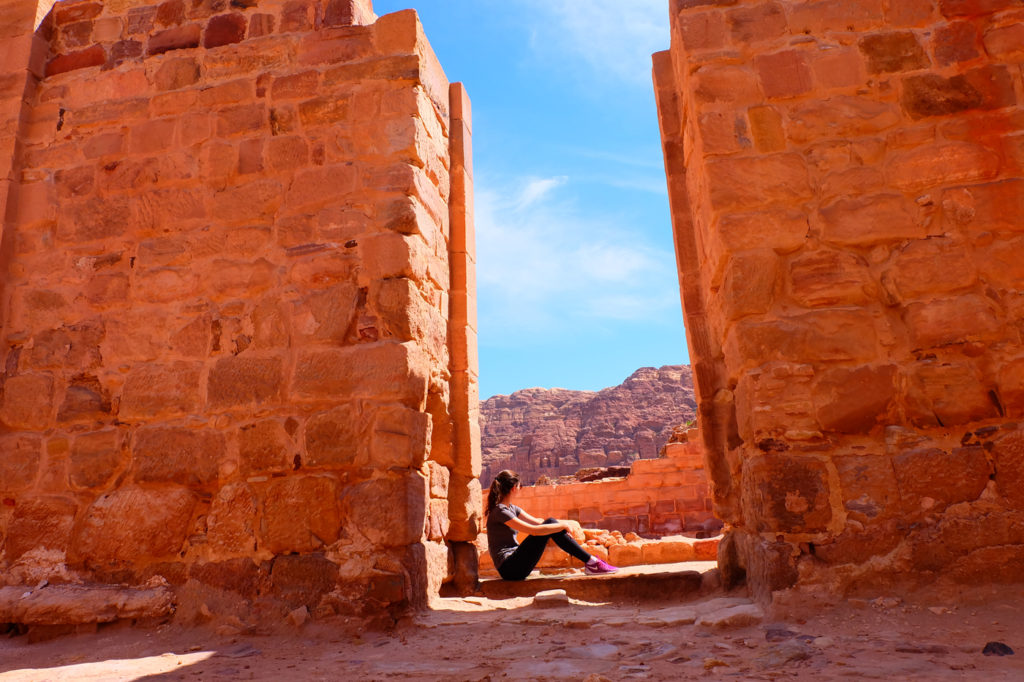My tips for solo travel for women. Photo of girl sitting in ruins in Petra, Jordan.
