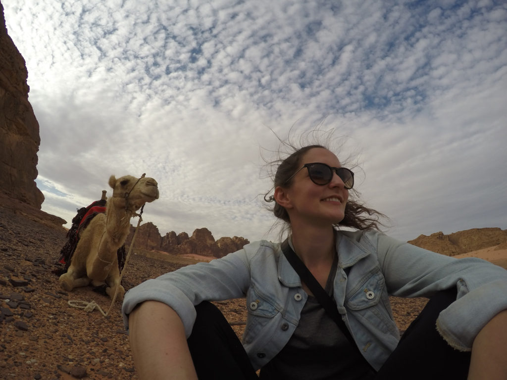Solo travel for women doesn't have to be intimidating. Photo of girl taking a selfie with a camel in Jordan.