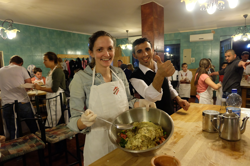 Cooking lesson at Petra Kitchen in Jordan. Girl holding up bowl with ingredients in it