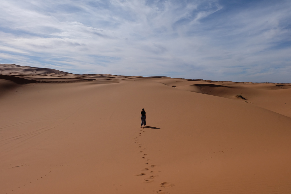 Girl standing in the middle of the Sahara Desert on a Morocco vacation