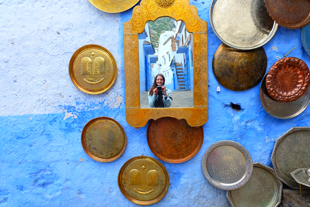 Girl taking photo in mirrors against a wall in Morocco.