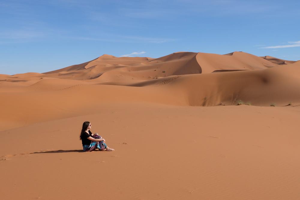 Girl in Sahara Desert in Morocco sitting on the sand.