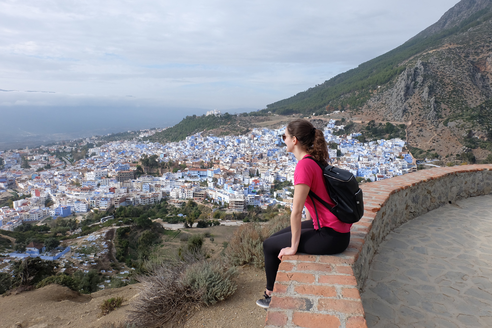 Girl sitting at lookout looking out over the Blue City in Morocco.