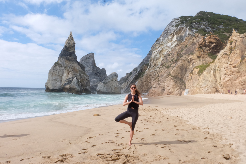 Girl doing a tree pose on a beach in Portugal. This article is sharing solo travel for women, and my biggest safety tips.