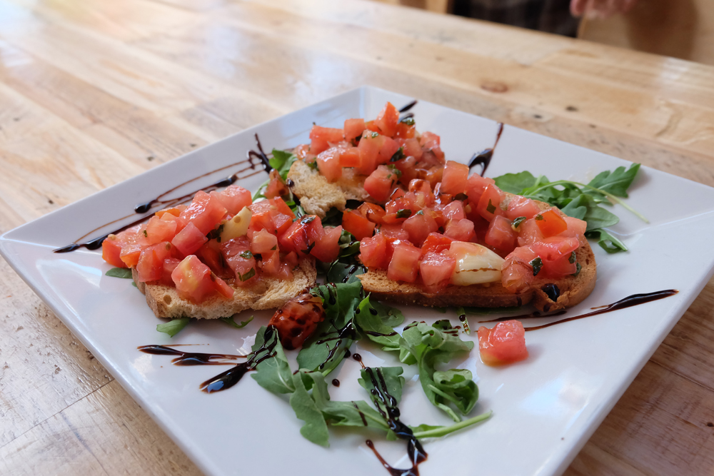 Bruschetta on a white plate with a balsamic drizzle. Enjoyed on my trip to San Francisco.