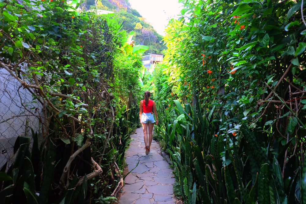 Lauren walking down a lush, green trail to the best place to stay in Lake Atitlan, Lush