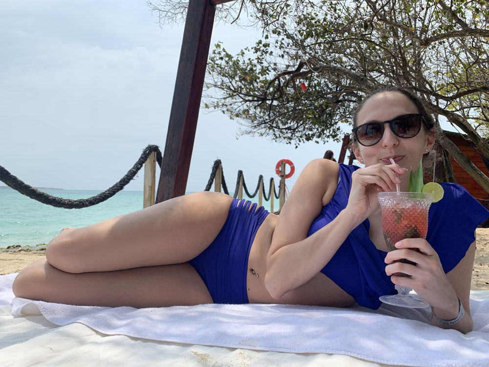 Lauren sitting. on a beach sipping a tropical drink on her trip to Colombia.