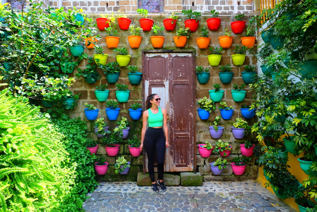 Girl standing in front of a colourful door full of plant pots on a trip to Colombia.