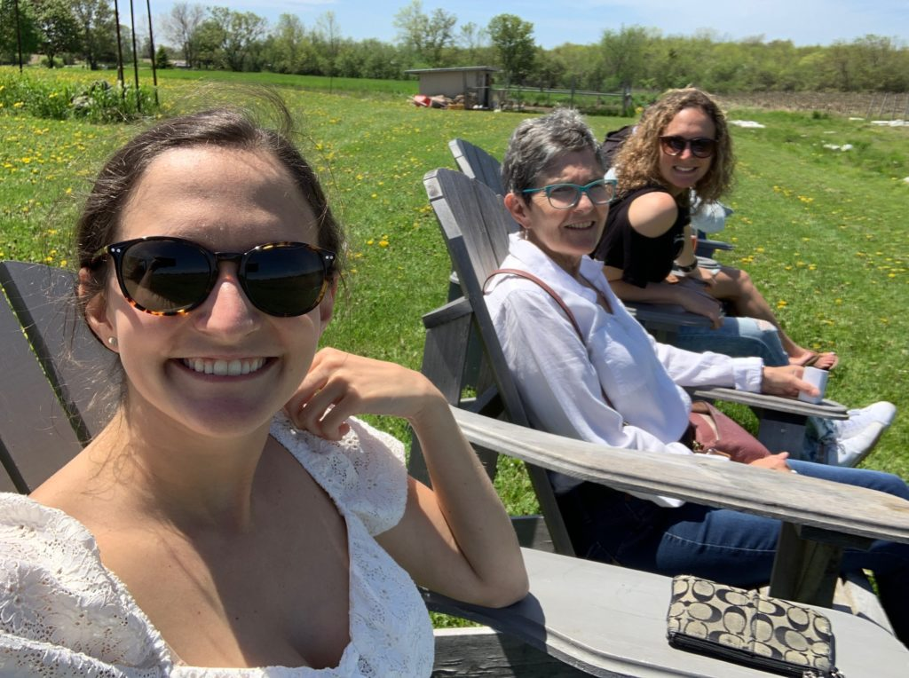 Mom and two daughters sitting on Muskoka chairs during a Prince Edward County vacation.