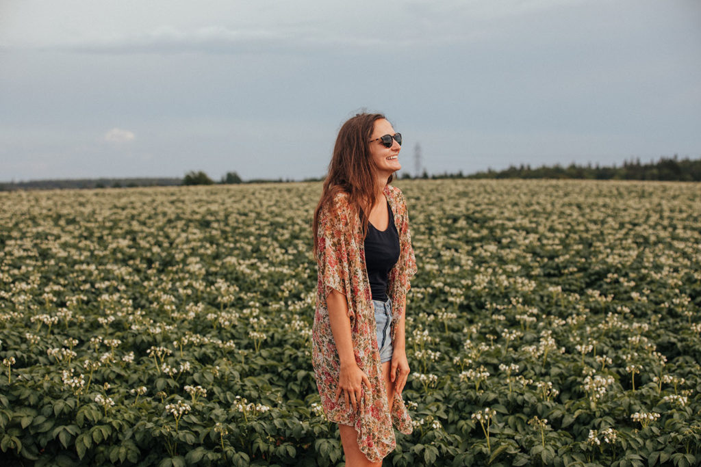 Girl standing in a potato field on a PEI vacation.