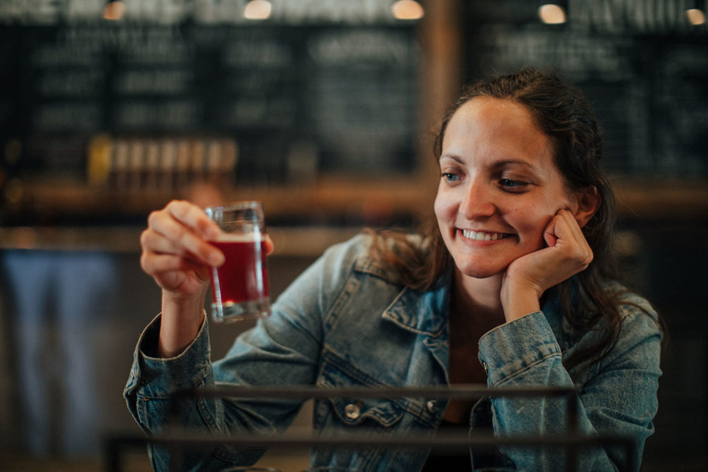 Girl staring at a sampling glass of craft beer.