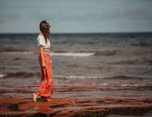 Girl on beach on a PEI vacation with wind blowing through hair.