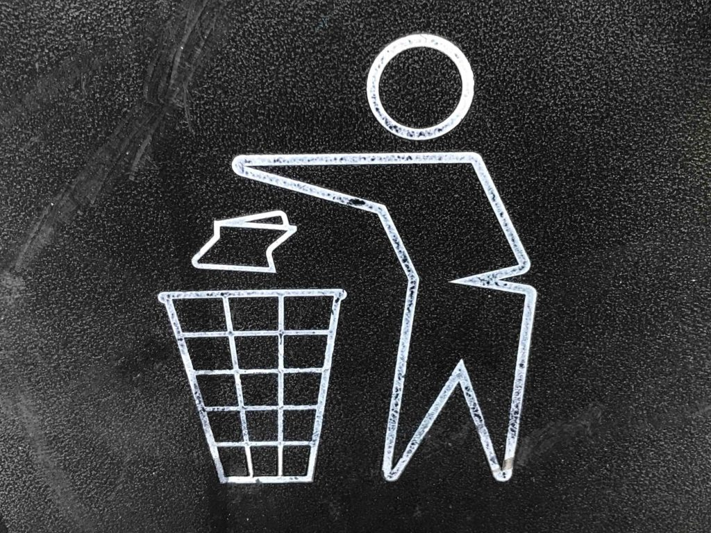 An illustration of a man throwing out garbage in a trashbin.