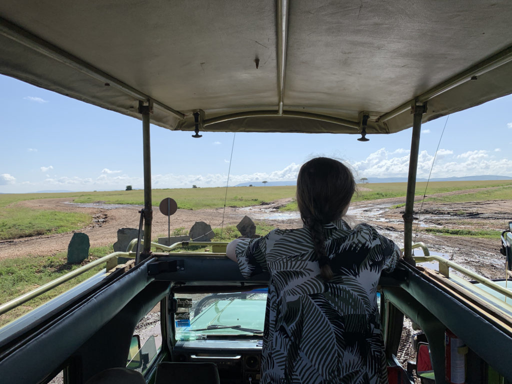 Lauren in Kenya looking out of a safari jeep into the wild.