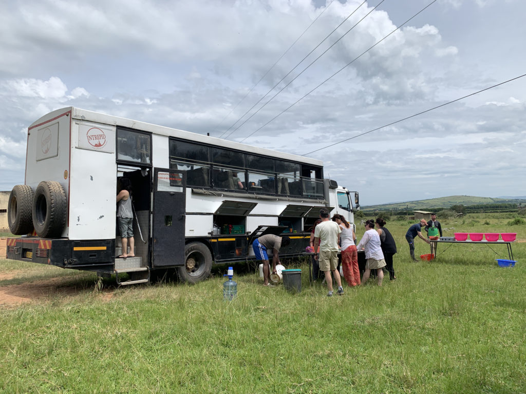Overland tour bus from Intrepid travel for a trip through East Africa parked on the side of the road.