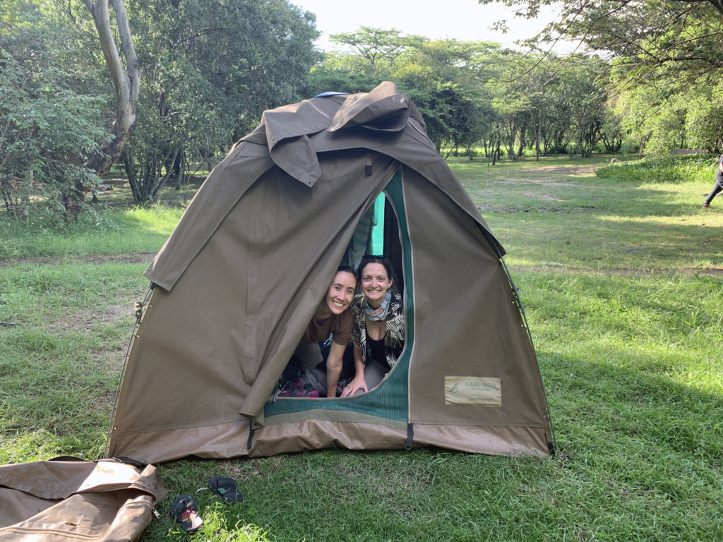 Two girls peaking out of a tent in East Africa.