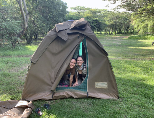 Two girls peaking out of tent on trip through East Africa