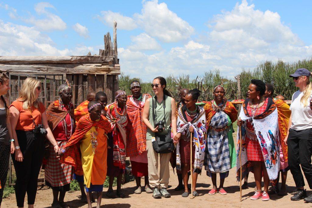 Tourists gathered with women from Maasai Mara in their village.