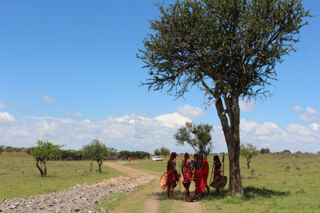 Members of the Maasai Mara tribe standing in a field next to a tree catching shade.