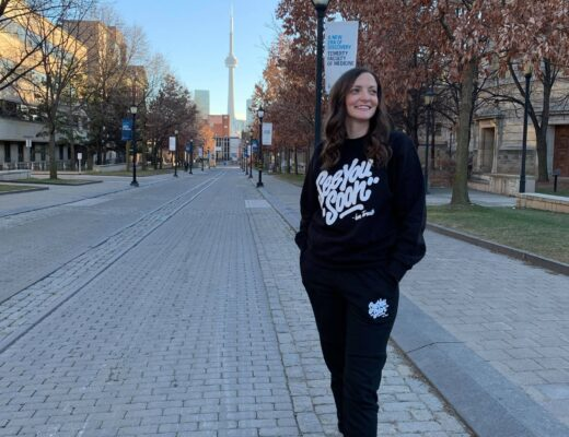 Lauren standing in Toronto with a See You Soon Toronto tracksuit on.